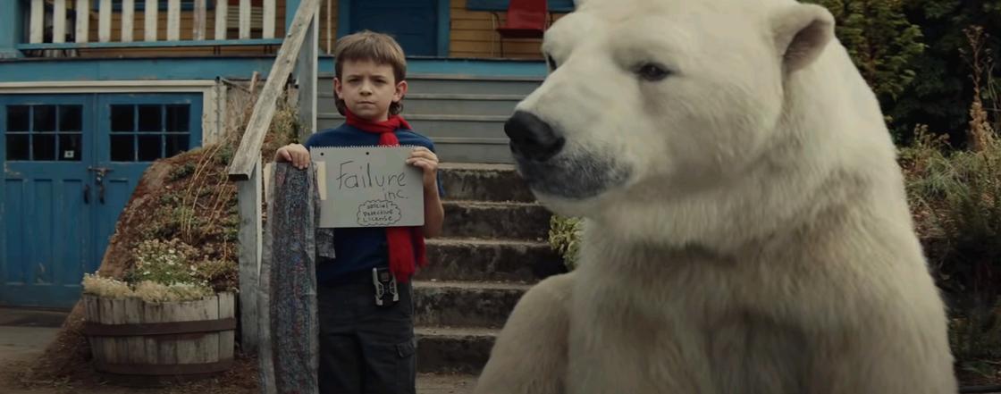 Кадр из фильма «Тимми Фейл: Допущены ошибки». Мальчик рядом с медведем держит лист с надписью