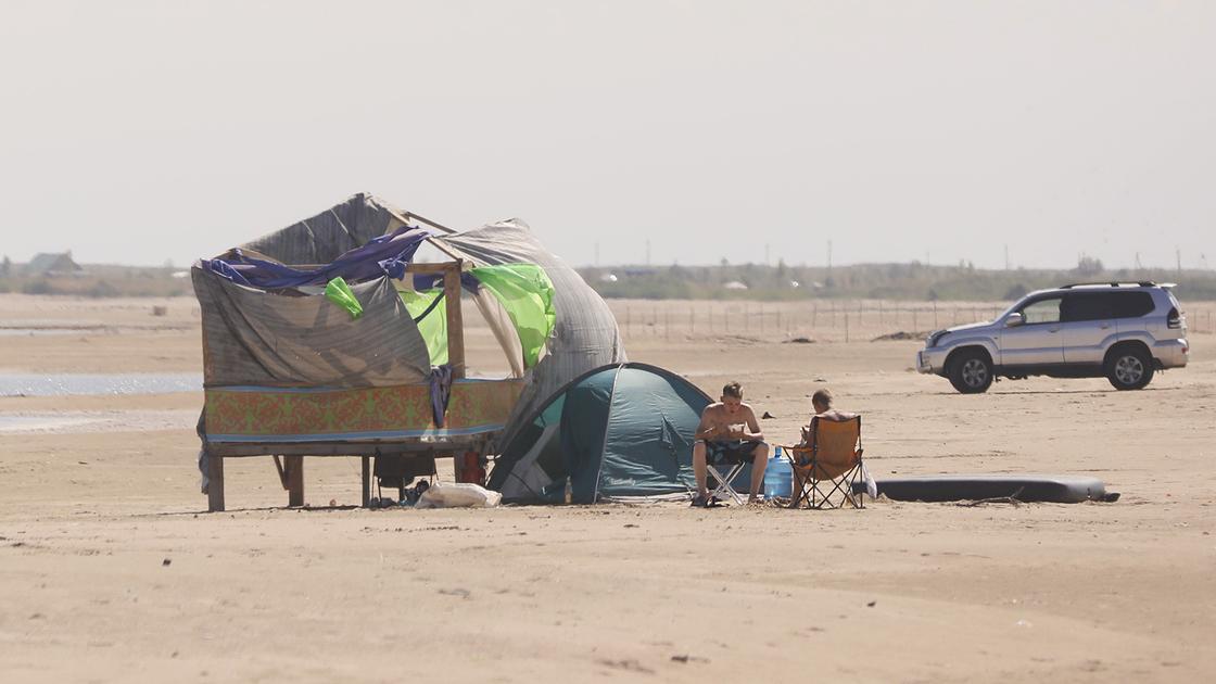 Люди сидят возле палатки