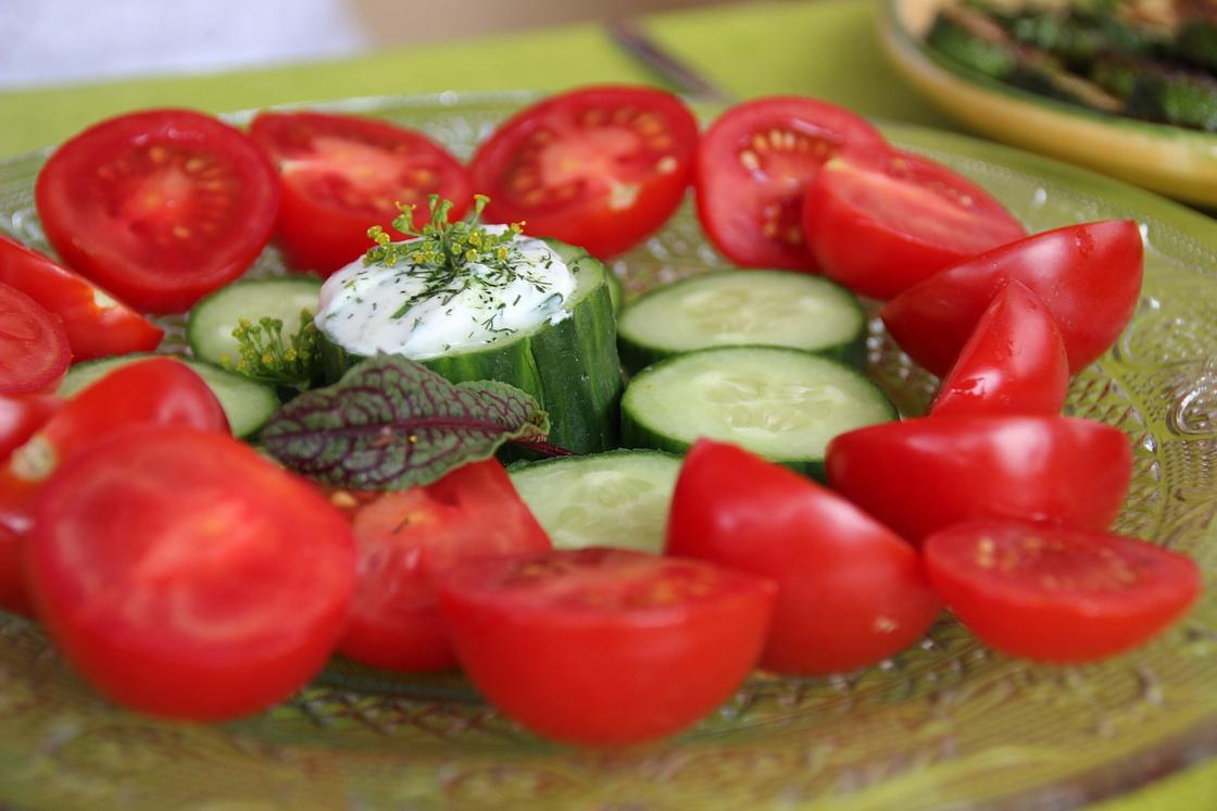 Нарезанные огурцы и помидоры на тарелке