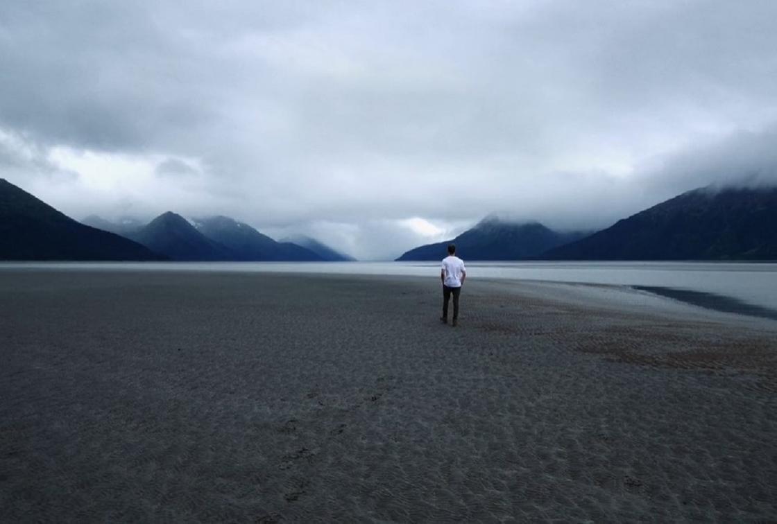 Парень идет по берегу горного озера