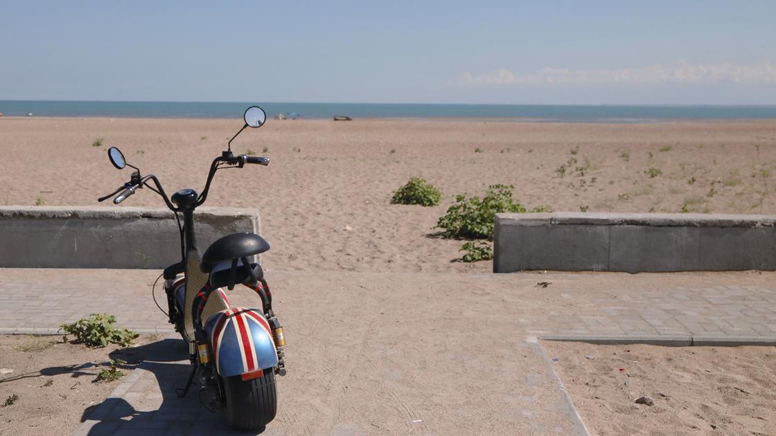Мопед стоит на пляже