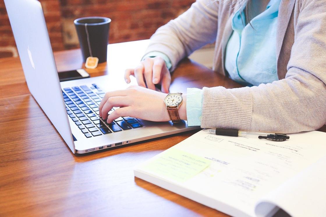 Человек работает за компьютером за столом