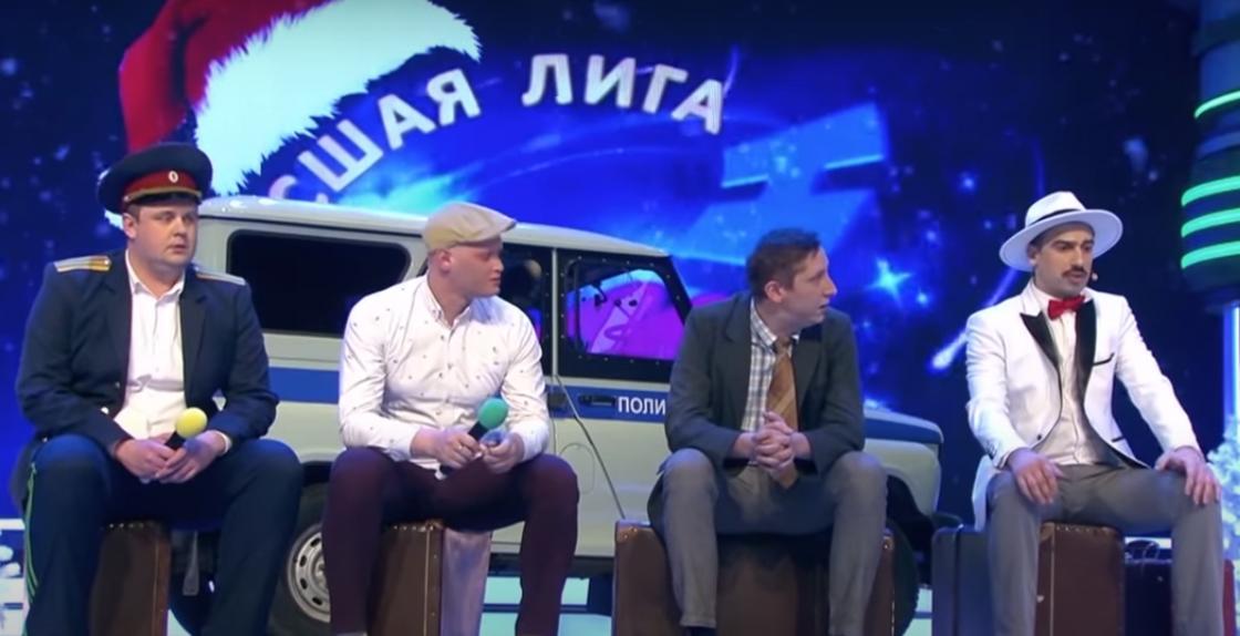 Чемпионы КВН 2020: «Русская дорога». Мужчины сидят на чемоданах на сцене