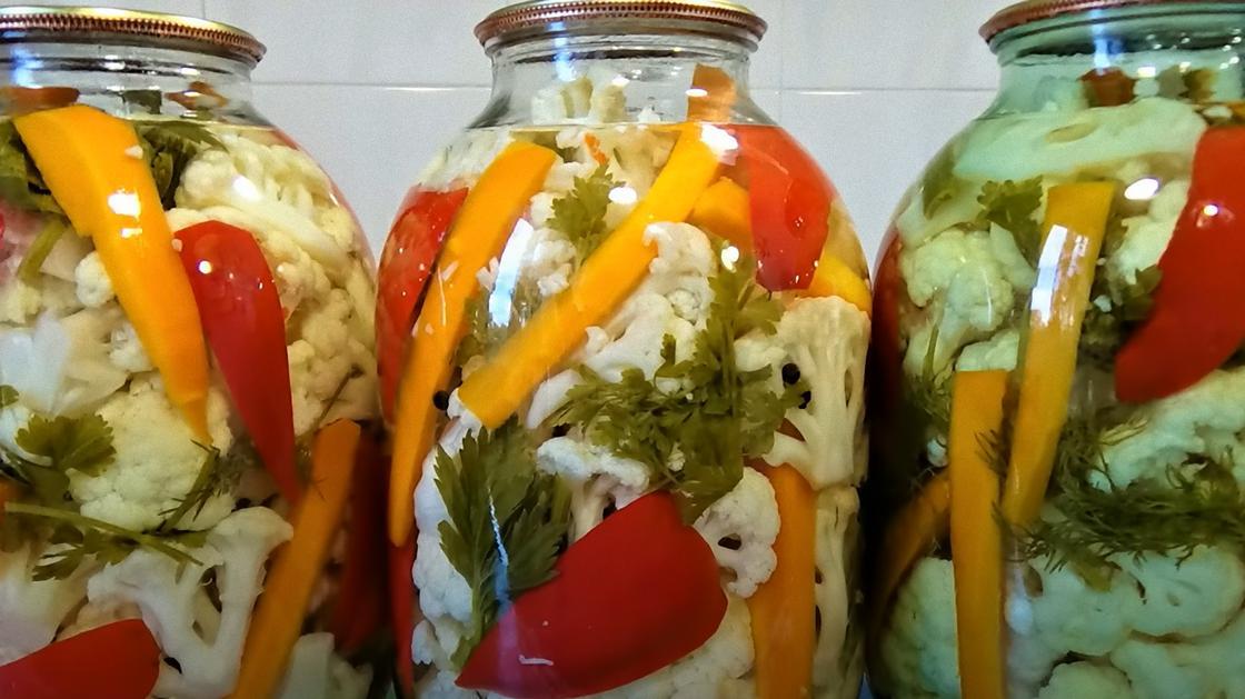 В трехлитровых банках цветная капуста, морковь, красный перец, зелень