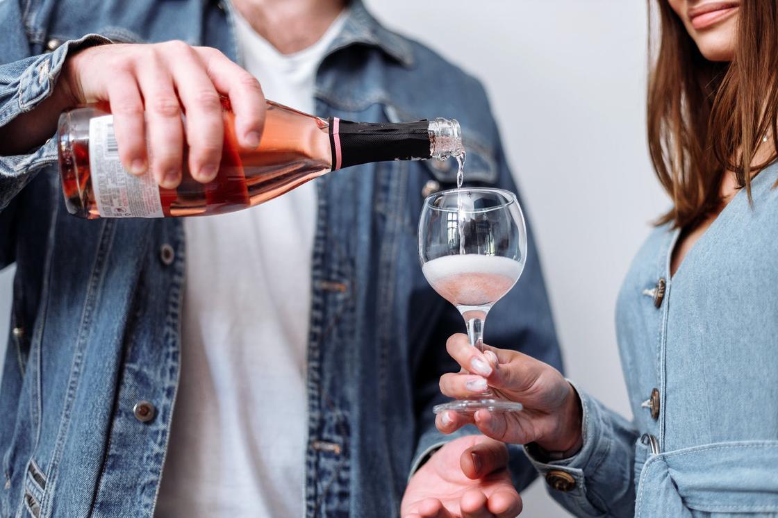 Мужчина в джинсовой куртке наливает алкоголь в бокал, который держит девушка в голубом