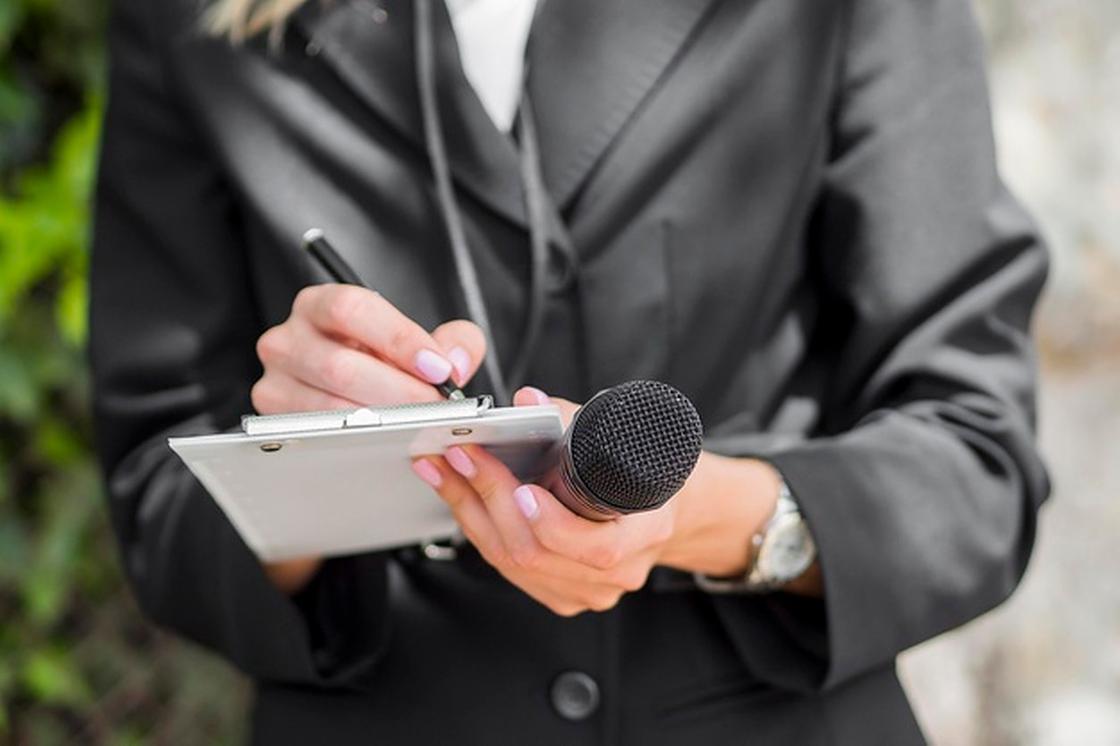Журналист с микрофоном и блокнотом