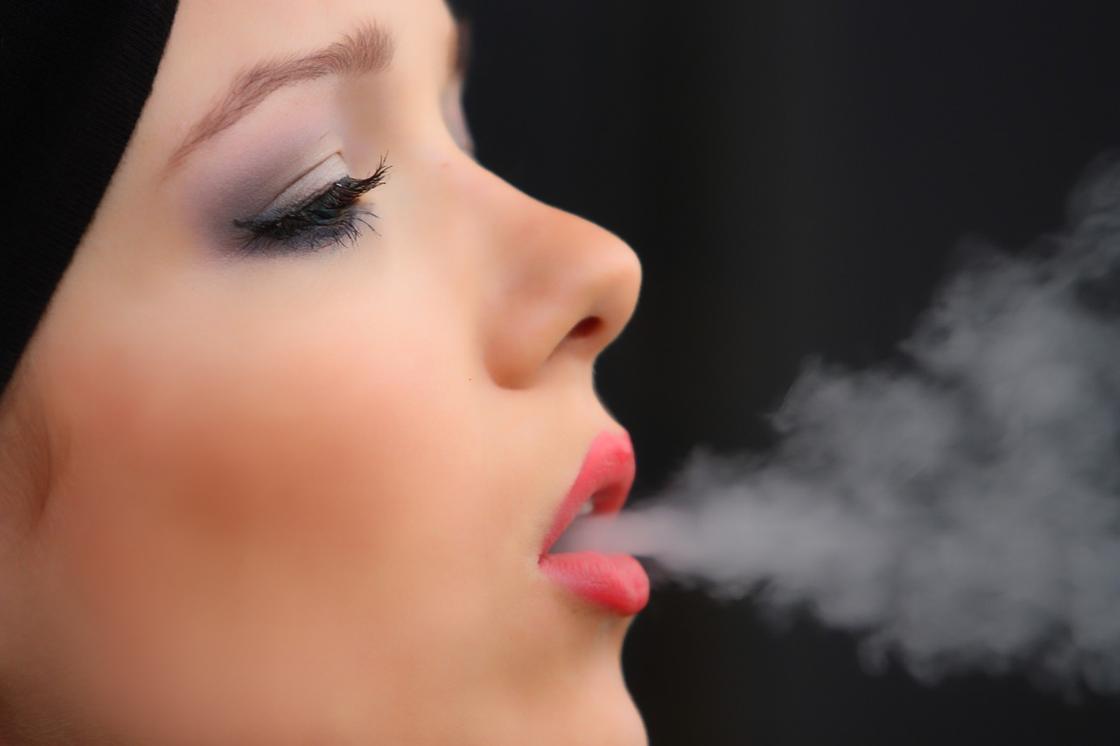 Женщина выпускает изо рта дым