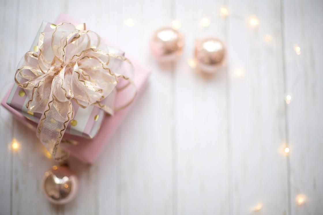 Новогодний подарок с лентой, елочные шары и гирлянда