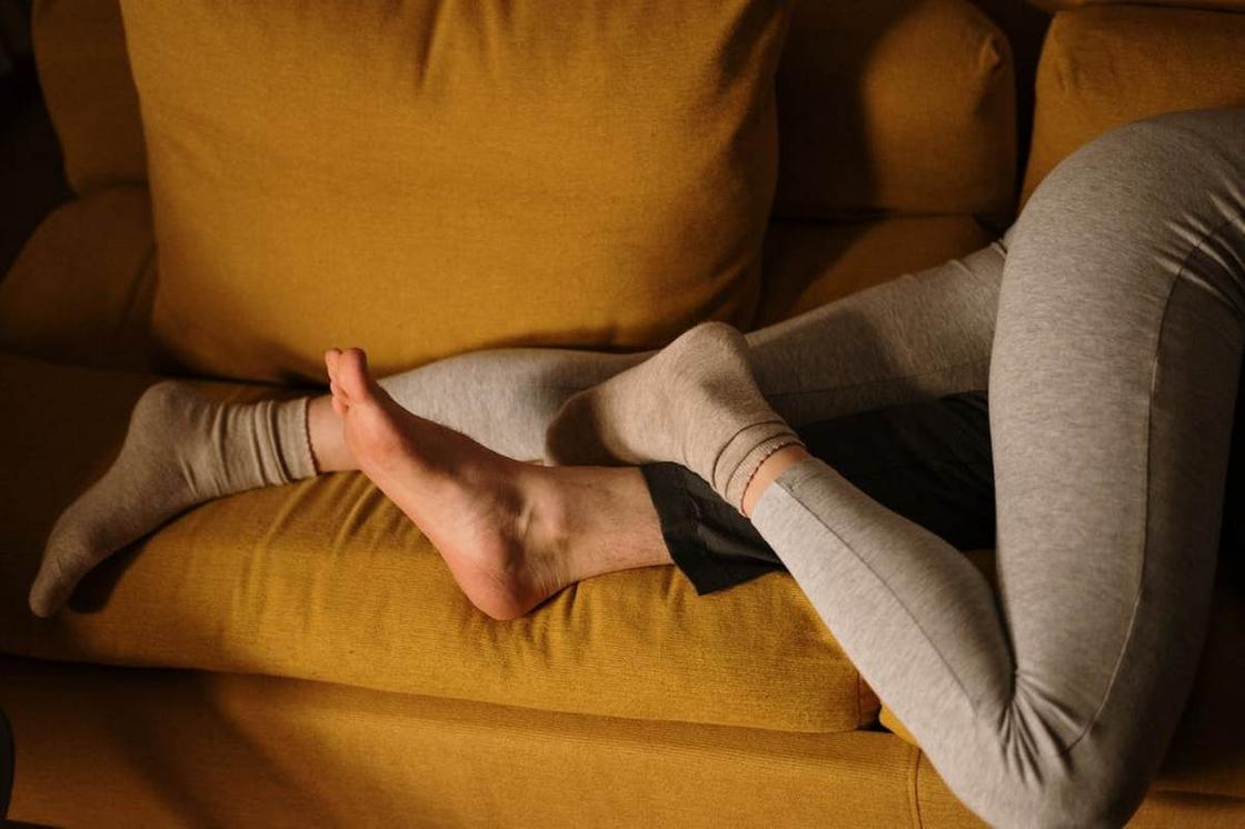 Мужские и женские ноги на диване горчичного цвета