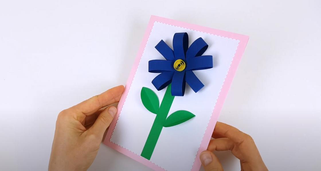 Девушка показывает открытку с объемным цветком