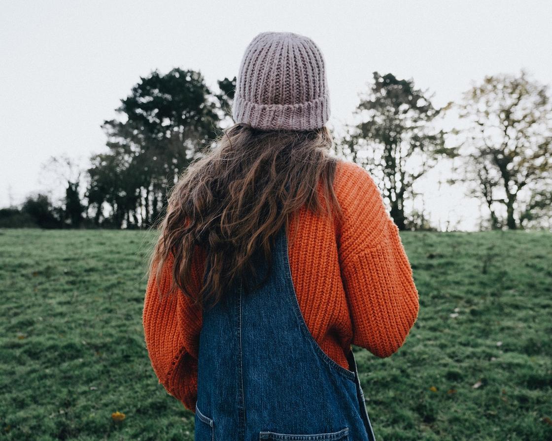 девушка в джинсовом комбинезоне и свитере