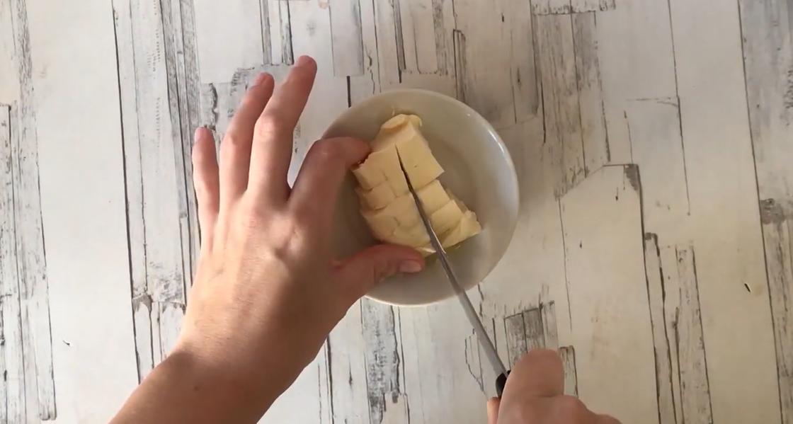 Масло нарезают на кусочки в тарелке на столе