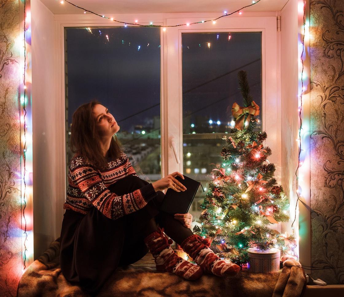 Девушка на подоконнике, украшенном гирляндой и елкой