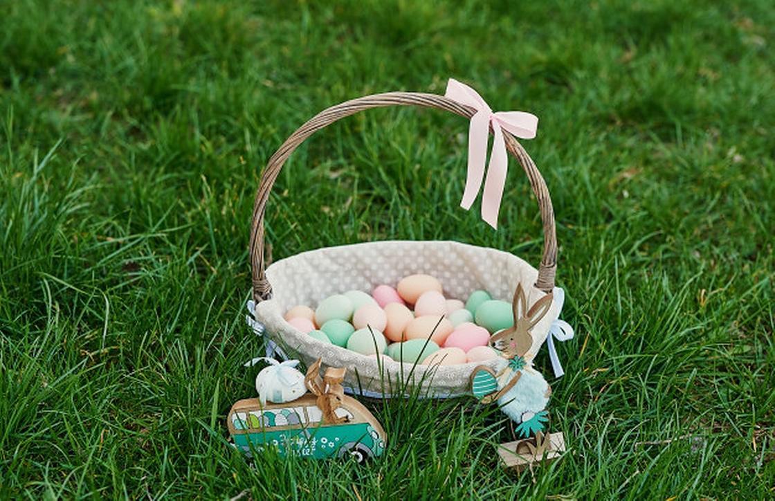 Пасхальная корзина с яйцами на зеленой траве