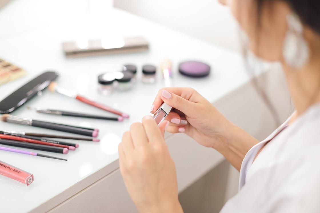 Женщина держит в руках блеск для губ, на столе все для макияжа