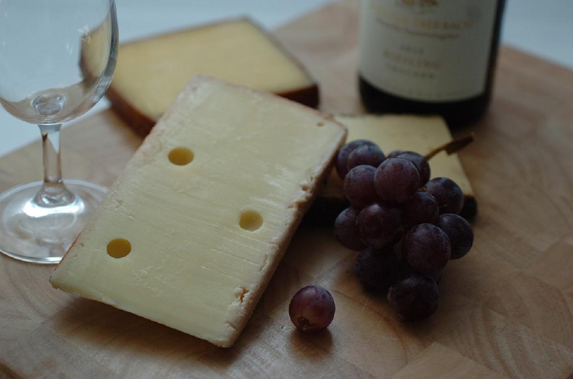 Бокал, сыр, бутылка вина и гроздь винограда