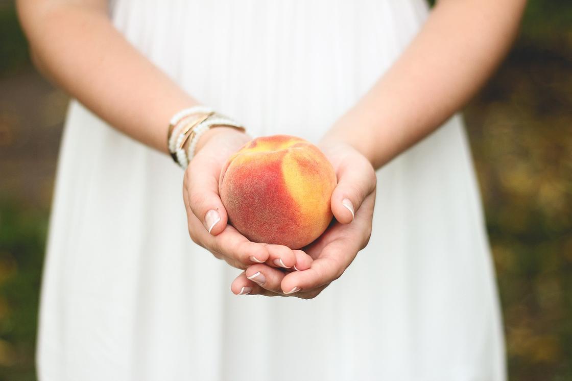 Персик в руках у девушки