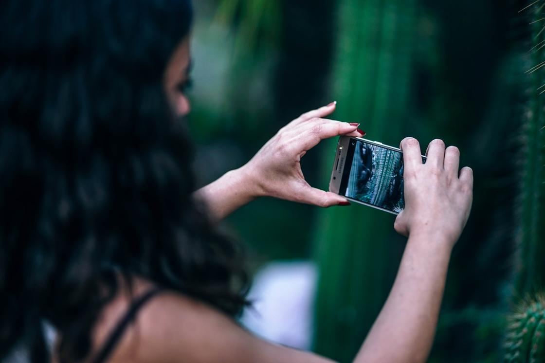 Девушка держит в руках смартфон и фотографирует