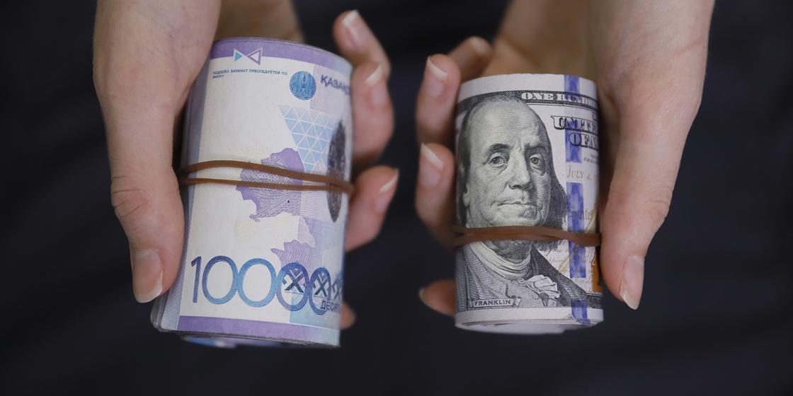 Женщина держит в руках тенге и доллары
