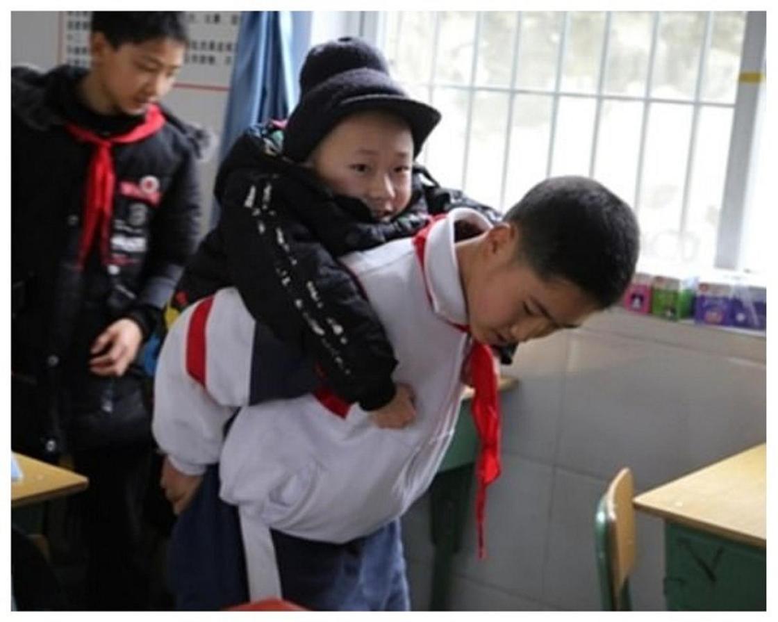 Алты жыл бойы досын мектепке арқалап апарған қытайлық оқушы елді сүйсінтті