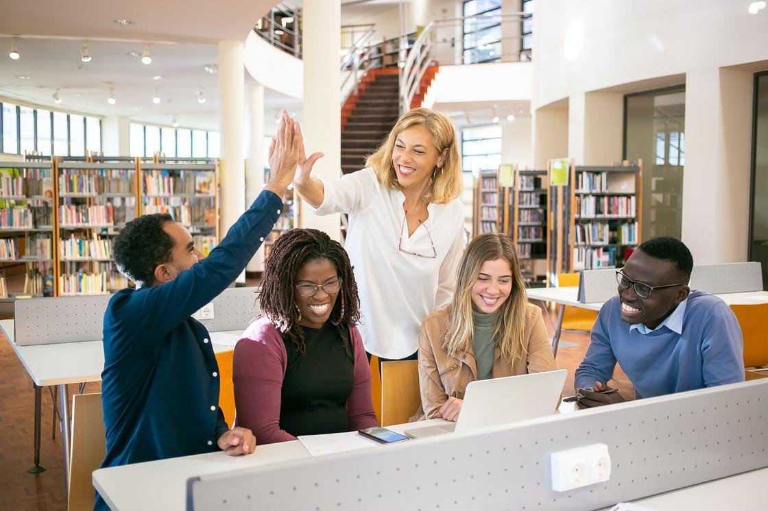 Группа студентов, сидящих в библиотеке, и их педагог