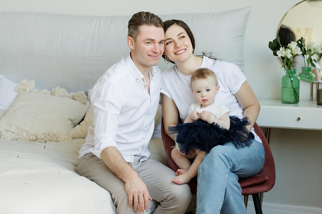 Родители с дочерью сидят на диване