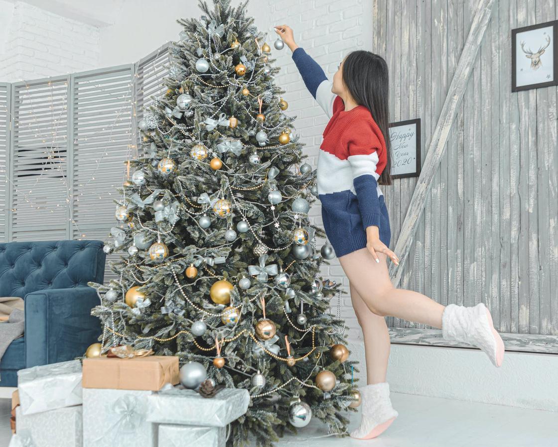 Девушка наряжает елку