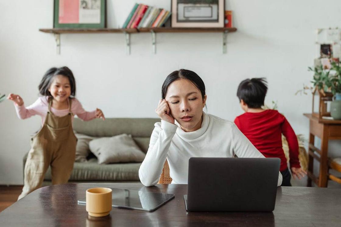 Уставшая мама сидит за компьютером, а двое ее маленьких детей бегают по комнате