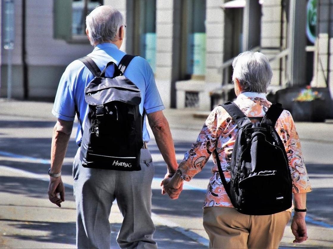 Пара пожилых людей держится за руки