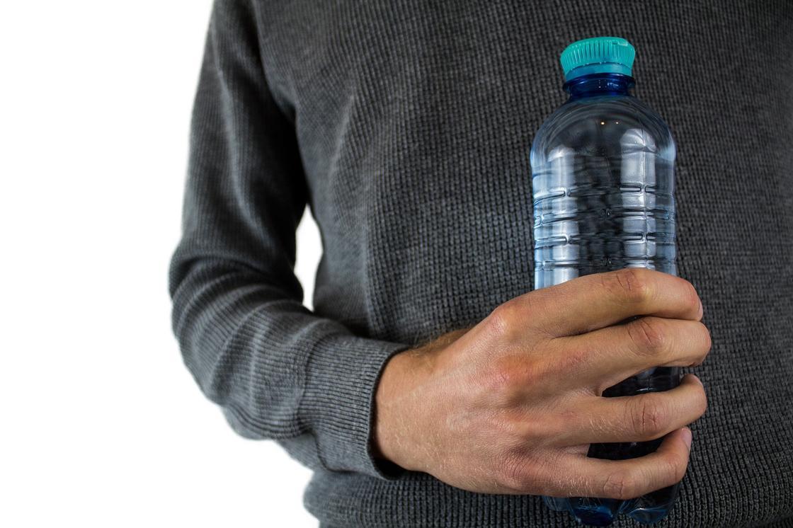 Мужчина держит бутылку с водой