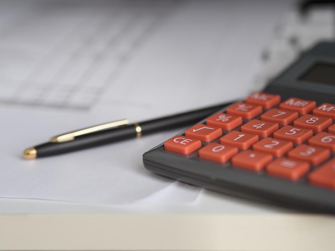 Калькулятор, ручка на столе
