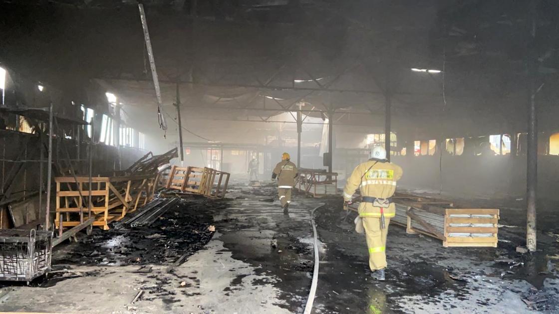 Пожарные ходят по сгоревшему складу