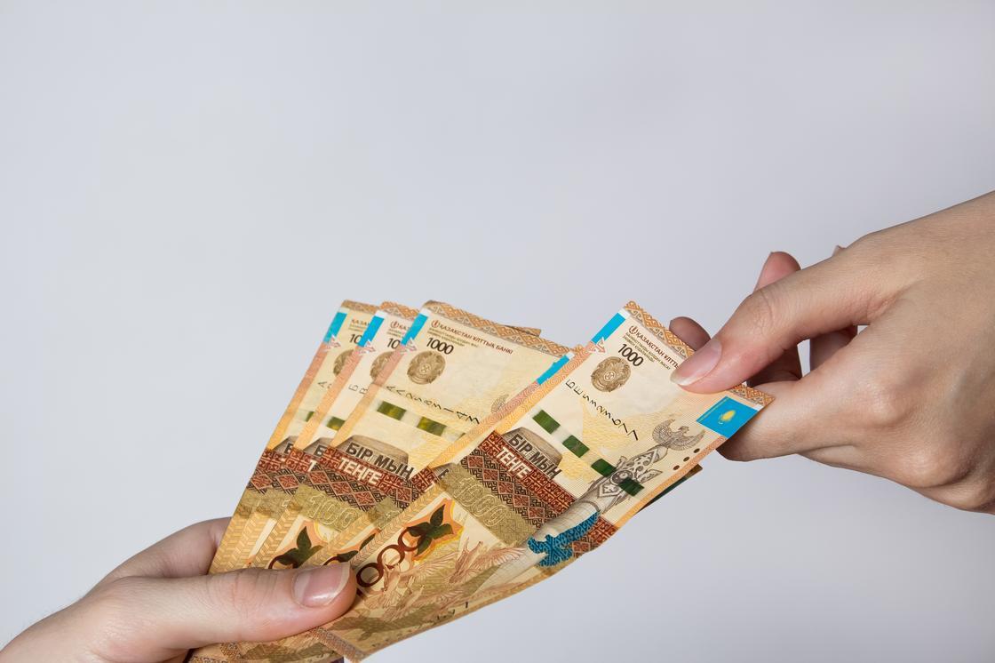 Девушка передает деньги другой девушке