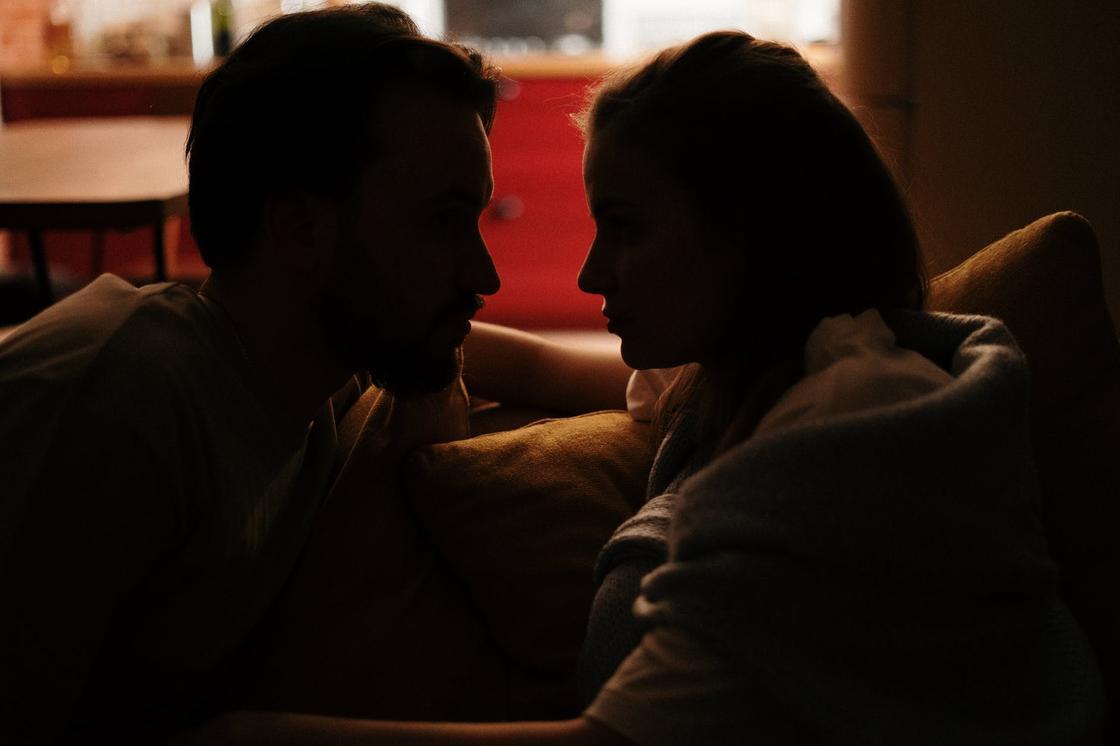 Мужчина и женщина смотрят друг на друга в полутьме