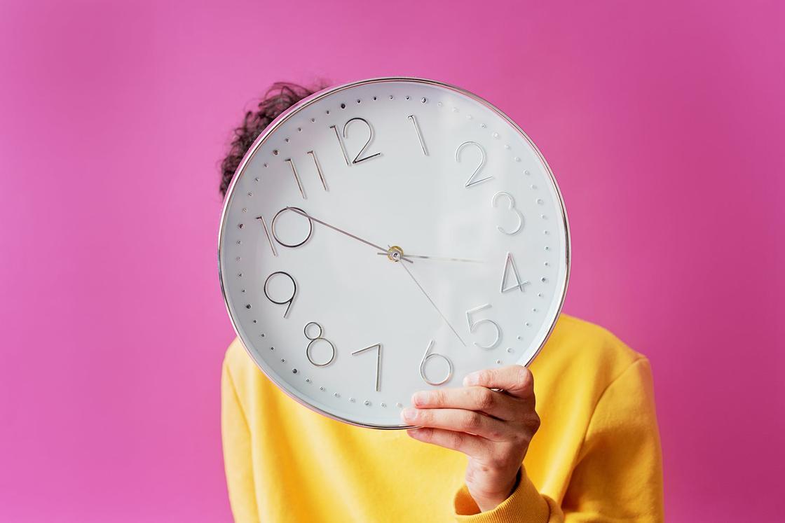 Человек в желтом закрывает лицо настенными часами на розовом фоне