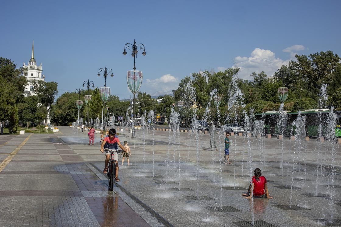 Дети бегают у фонтана