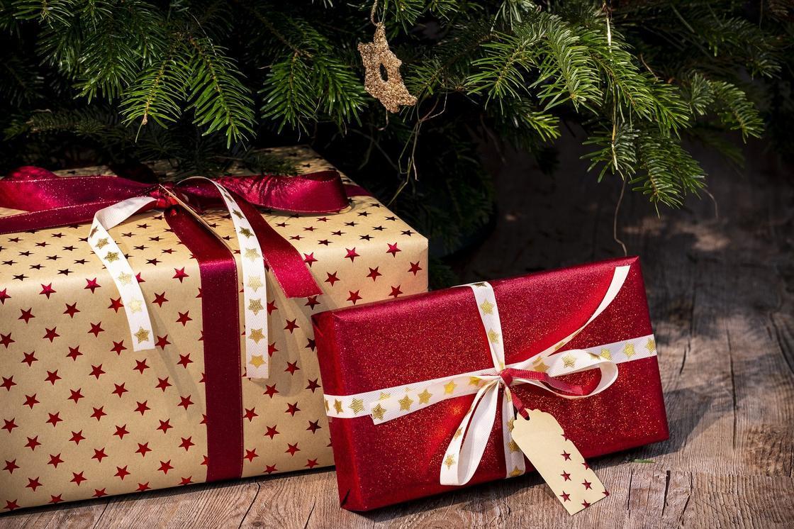 Новогодние подарки в подарочной бумаге под елкой