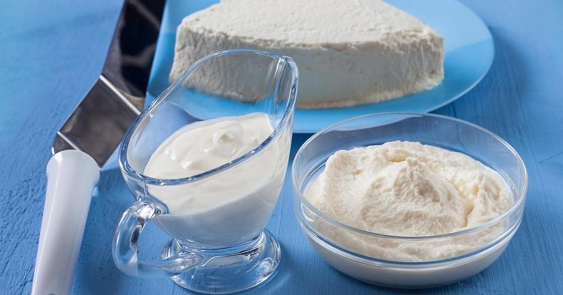 Ингредиенты для крема: творог на тарелке, сливки и сахарная пудра