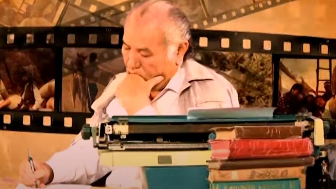 Дулат Исабеков пишет рядом со стопкой книг