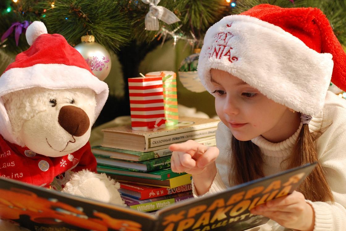 Девочка и плюшевый мишка рядом с новогодней елкой