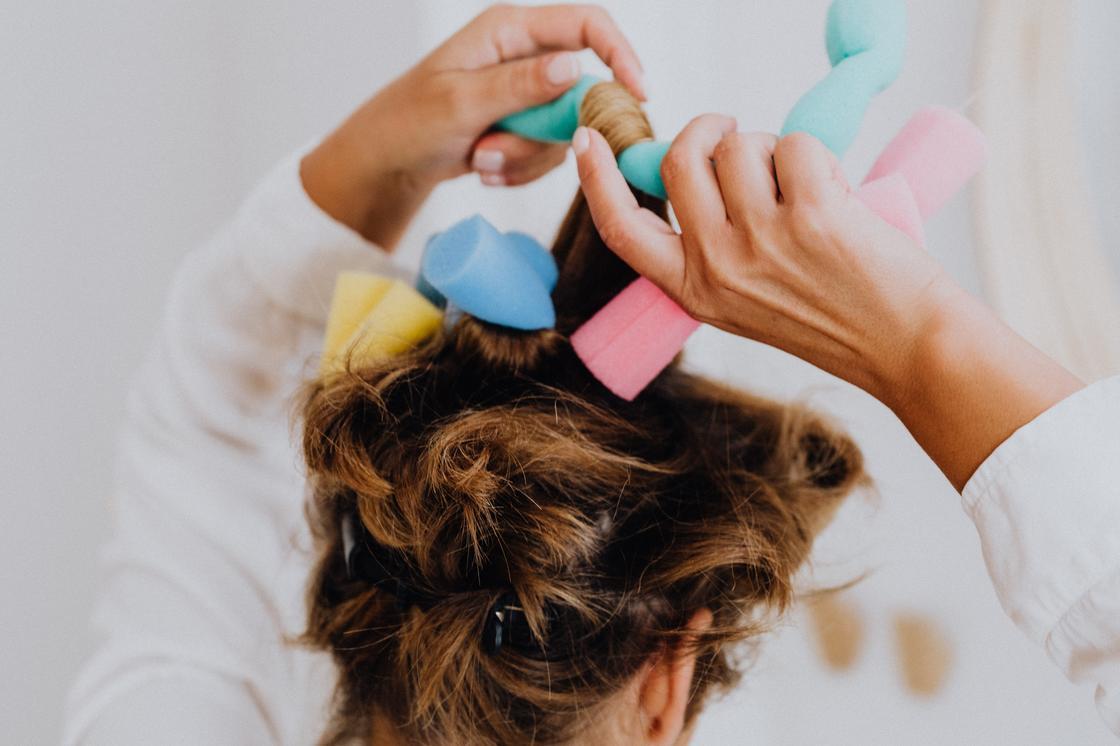 Женщина накручивает волосы на бигуди