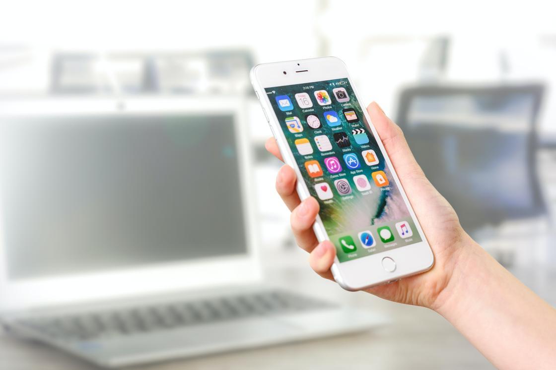 Телефон в руке на фоне ноутбука
