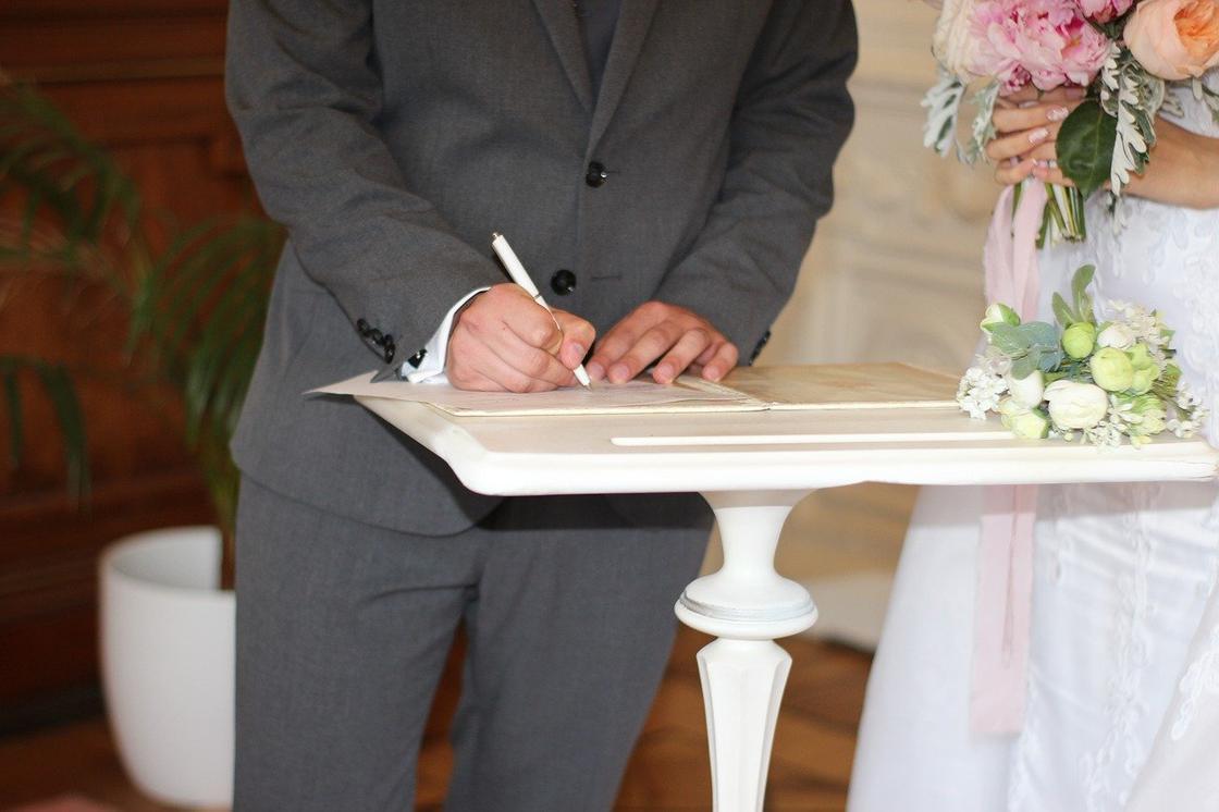 Мужчина расписывается в брачном свидетельстве