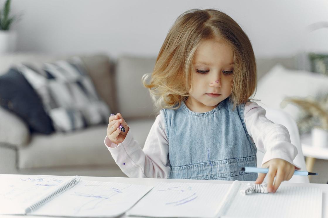 Девочка в голубом сарафане сидит за столом с ручкой в руках