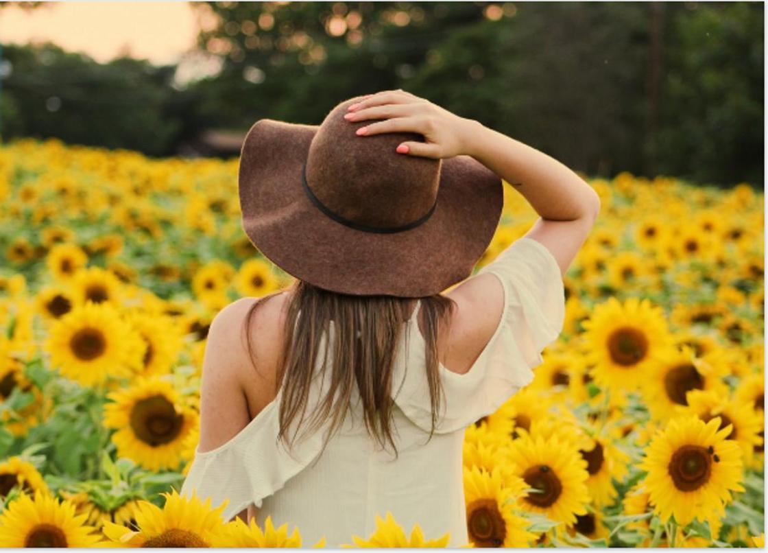 Девушка в шляпе и белом платье на фоне подсолнухов