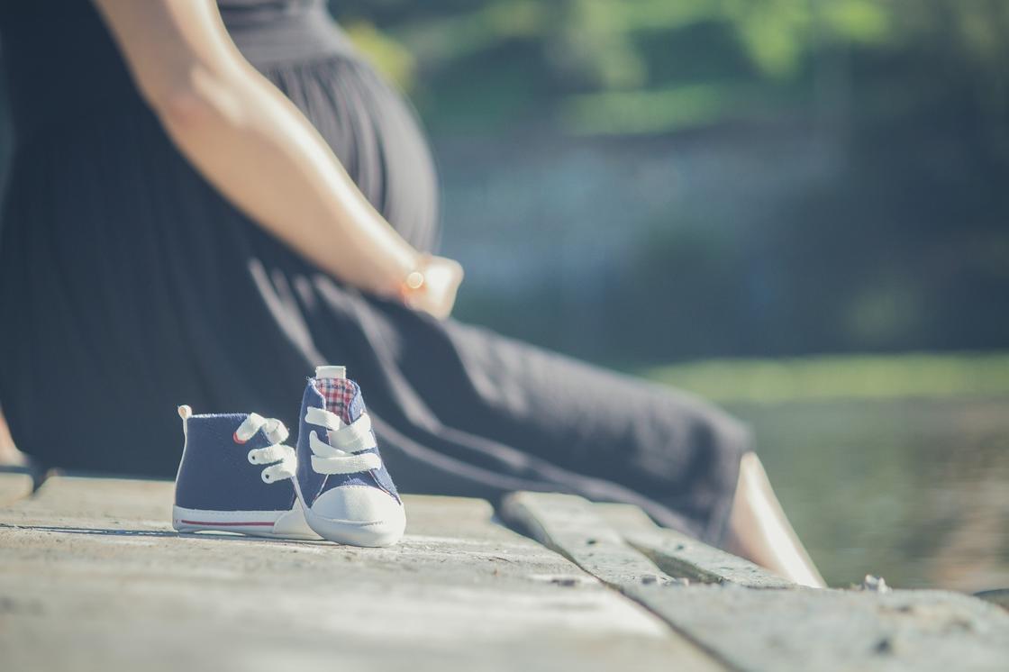 Детские ботиночки на фоне беременной женщины