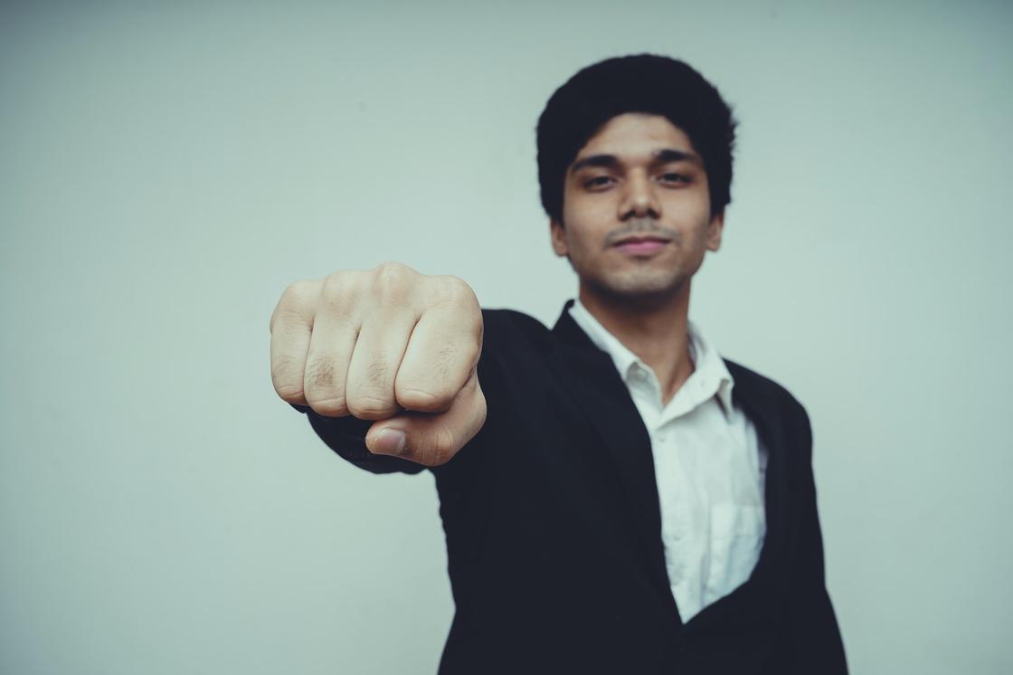 Мужчина в костюме показывает кулак