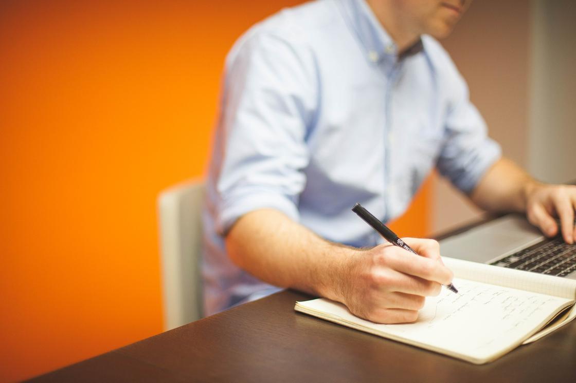 Мужчина делает записи в тетради с экрана ноутбука