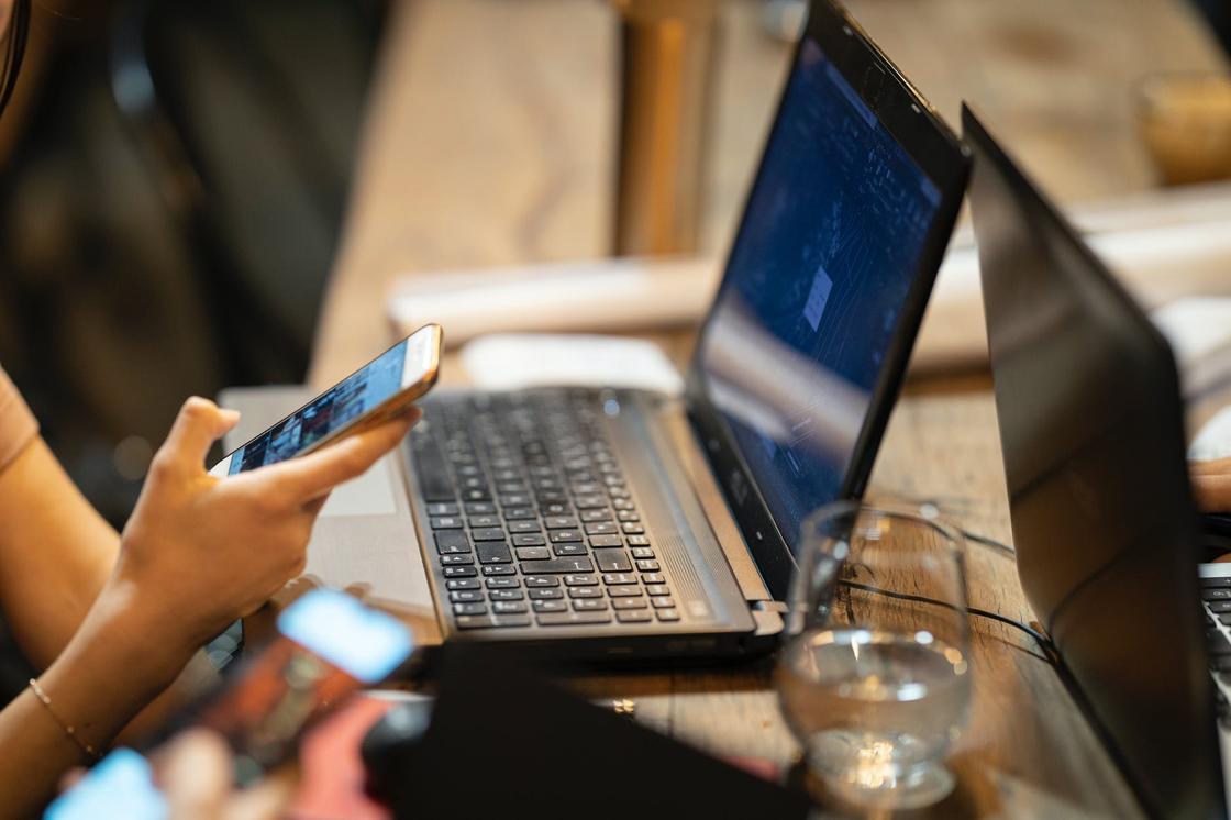 Мужская рука с телефоном рядом с ноутбуком и стаканом воды