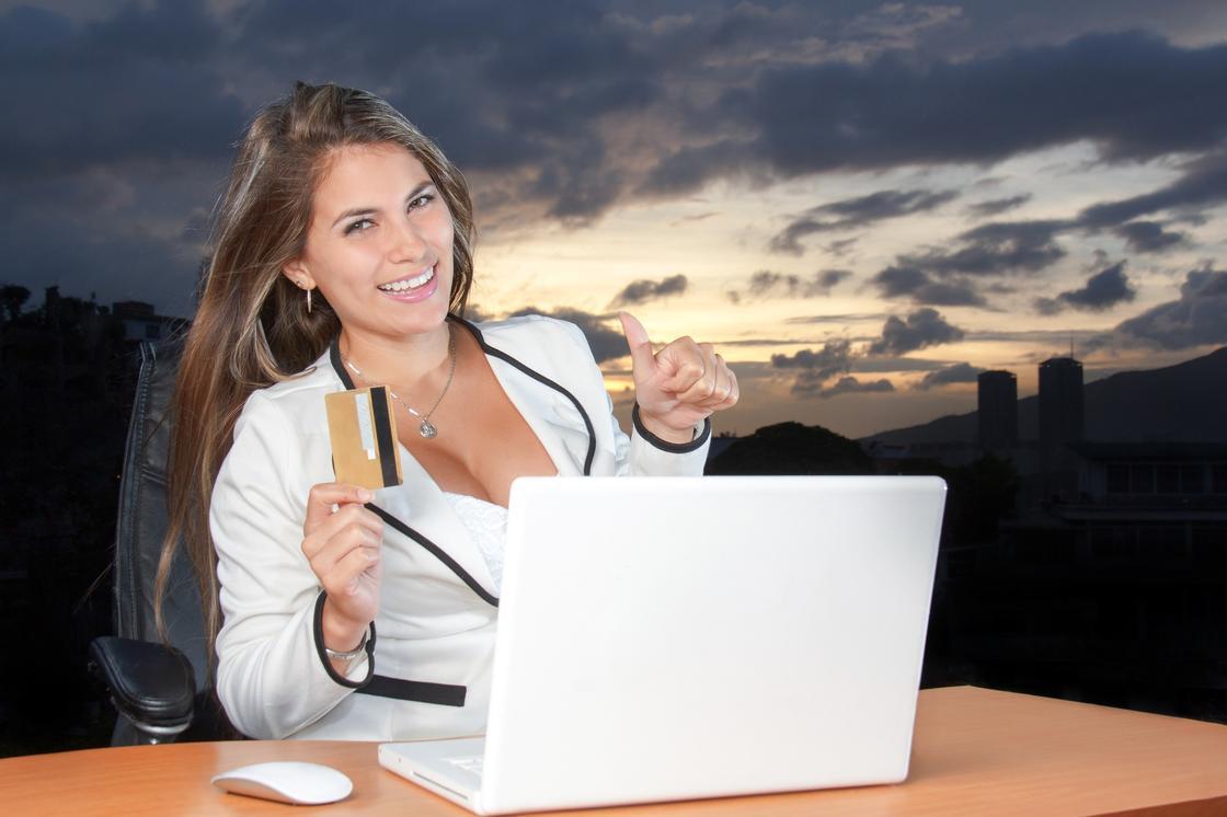 Девушка с кредиткой в руке улыбается, сидя перед ноутбуком